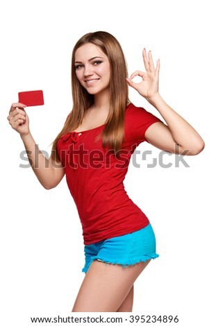 Beautiful bright smiling confident girl showing red card in hand and gesturing OK sign, over white backround - stock photo