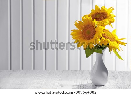 Beautiful bright sunflowers in vase on wooden background - stock photo