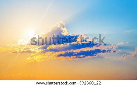 Beautiful bright sunset. Colorful sky with cumulus clouds and bright sun. - stock photo