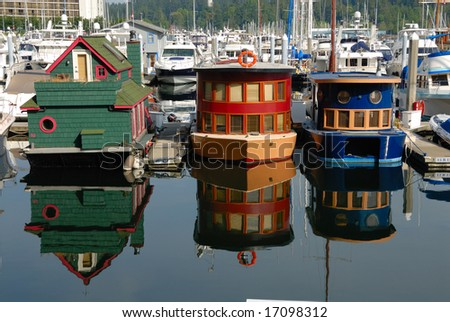 beautiful brightly painted houseboats with reflections in Vancouver marina - stock photo