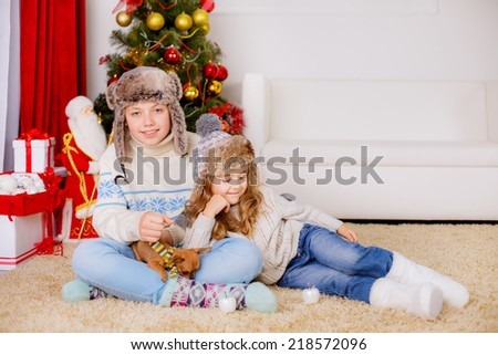 Beautiful brother and sister in a room near the Christmas tree - stock photo