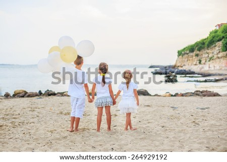 Beautiful brother and sisters play with a beach balloons outdoors  - stock photo