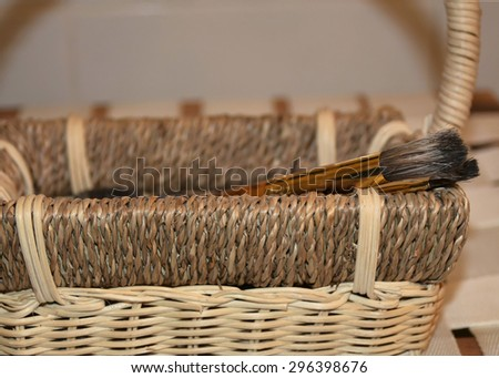 Beautiful brown basket and paintbrushes - stock photo