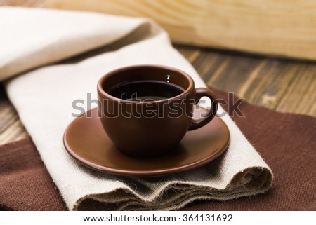 Beautiful brown cup with saucer of aromatic fresh hot strong black coffee strong drink for breakfast and break on light and dark textile studio closeup, horizontal picture - stock photo