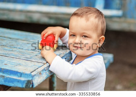 Beautiful brown-eyed little boy playing with a red plastic toy machine outdoors - stock photo