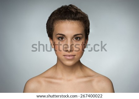 Beautiful brown-eyed natural girl on gray background - stock photo