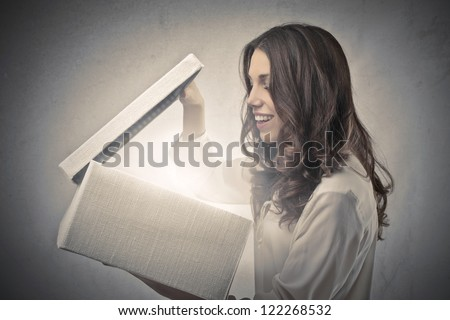 Beautiful brown girl watching in a box something bright - stock photo