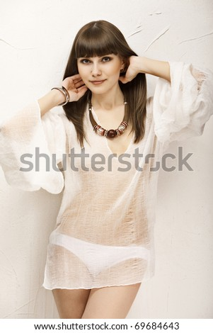 Beautiful brown-haired girl dressed in white on a background wall