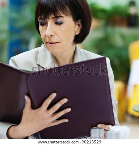 Beautiful brown-haired woman sitting cafe reading menu - stock photo
