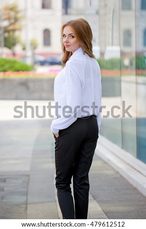 Beautiful brown-haired young woman wearing clothes and walking on the street, girl