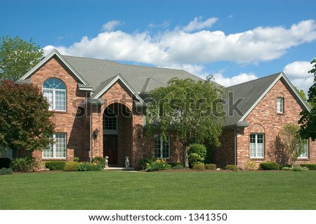 Beautiful brown two story brick home. Very colorful photo with blue sky and green grass. Typical new home in the suburbs of the United States. Just one of many home or house photos in my gallery. - stock photo