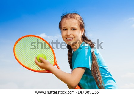 Beautiful brunet 10 years old little girl with tennis racquet - stock photo