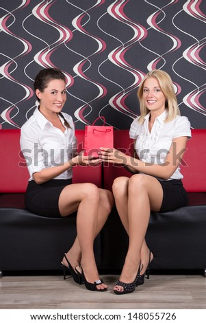 beautiful brunette and blond sitting on the sofa with gift bag - stock photo