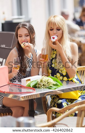 Beautiful brunette and blonde woman sitting  in outdoor cafe with a glass of wine. Day light. Life style.