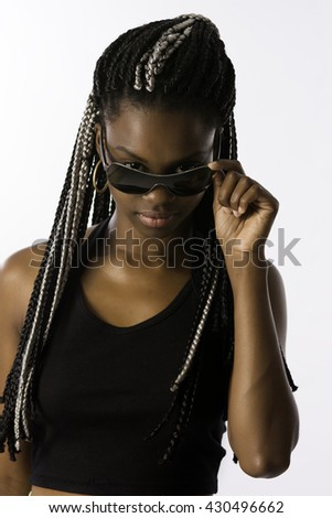 Beautiful brunette Brazilian woman, afro descendant, with long and braided hair, wearing sunglasses, in a white background. - stock photo