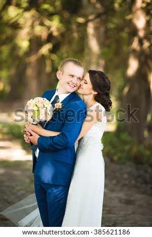 Beautiful brunette bride in elegant dress and handsome groom in blue suit at wedding day lovely hugging outdoors on nature. Bridal couple embracing in sunny green park. Loving wedding couple. - stock photo