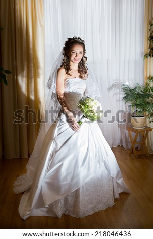 beautiful brunette bride in elegant white dress hold her bridal bouquet in hands portrait - stock photo