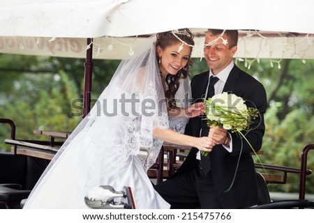 beautiful brunette bride in white wedding near her handsome young groom in black suit stand in the park car - stock photo