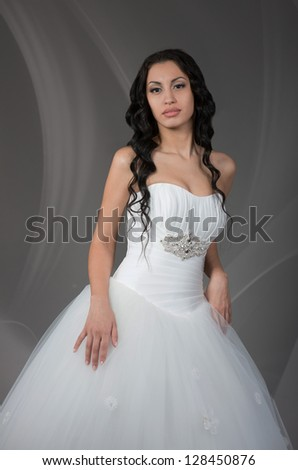 Beautiful brunette bride posing for photo, on grey background - stock photo
