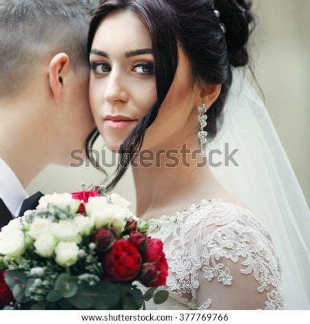Beautiful brunette bride with wedding bouquet smiling, while hugging groom closeup - stock photo