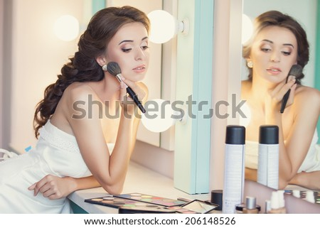 Beautiful brunette bride with wedding makeup and hairstyle, attractive newlywed woman have final preparation for wedding. Bride makeup. - stock photo