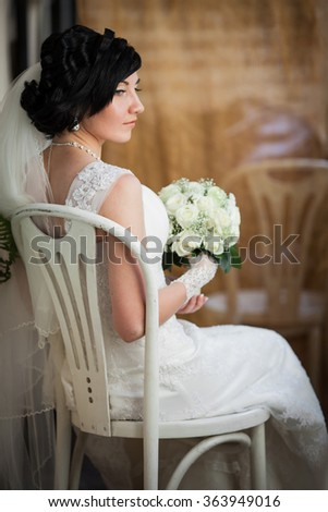 Beautiful brunette bride with white roses bouquet in elegant dress sitting on vintage white chair