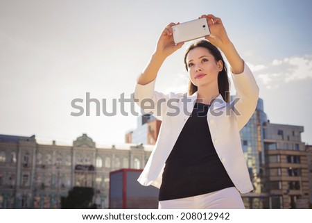 Beautiful brunette business woman in white suit photographing selfie on a tablet in her hands outdoors. copy space - stock photo
