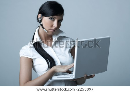 Beautiful brunette business woman with wireless headset and laptop computer isolated on clear background