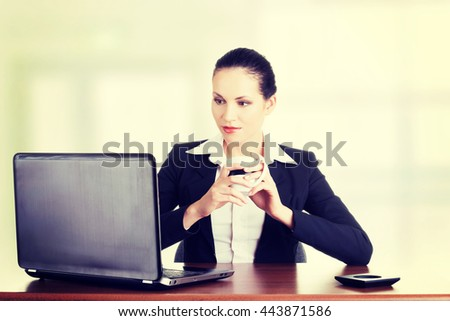 Beautiful brunette businesswoman working on laptop - stock photo