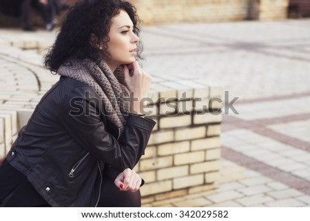 Beautiful brunette caucasian woman in leather jacket and scarf walking on european city in evening. cold weather. copy space