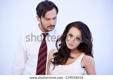 Beautiful brunette Caucasian woman with her handsom boyfriend behind her - stock photo
