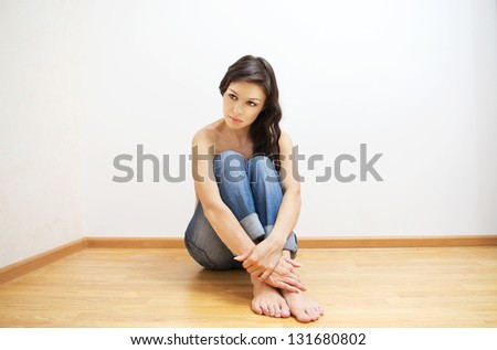 Beautiful brunette caucasian woman without shirt sitting on the floor.