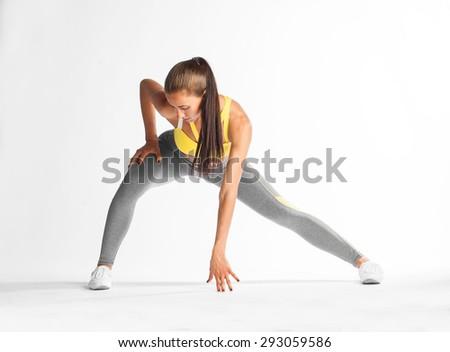 beautiful brunette doing step aerobics on white background - stock photo