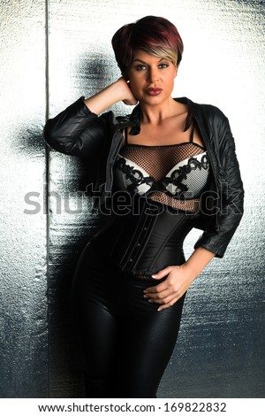 Beautiful brunette dressed in black leather and a white bra - stock photo