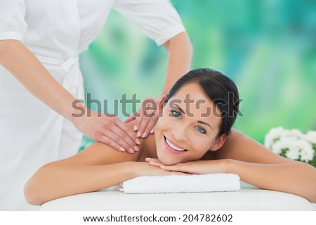 Beautiful brunette enjoying a back massage smiling at camera at a luxury spa - stock photo
