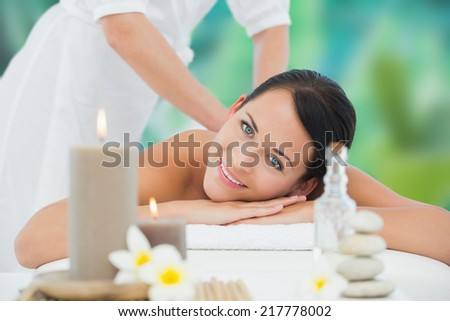 Beautiful brunette enjoying a back massage smiling at camera at a luxury spa - stock photo