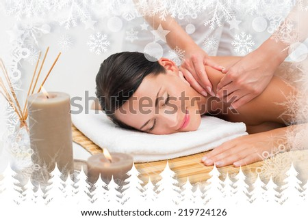 Beautiful brunette enjoying a shoulder massage smiling at camera against fir tree forest and snowflakes