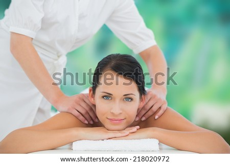 Beautiful brunette enjoying a shoulder massage smiling at camera at a luxury spa - stock photo