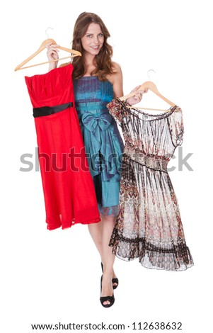 Beautiful brunette fashion model with a choice of dresses which she is holding up on hangers isolated on white - stock photo