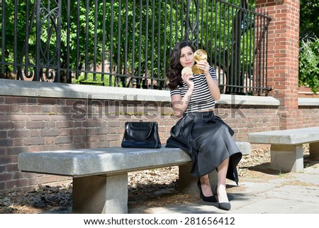 Beautiful brunette female model in vintage blouse and skirt sitting on a park bench applies make-up from vintage compact - stock photo