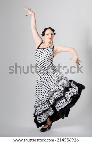 beautiful brunette female young beautiful brunette female spanish flamenco dancer in black and white flamenco dress dancing in studio on gray background - stock photo