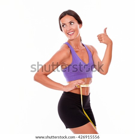 Beautiful brunette gesturing thumbs up, looking away and smiling while measuring her waist wearing violet and black gymnastic clothing and her hair tied back, isolated - stock photo