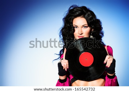 Beautiful brunette girl dancer posing with vinyl record.