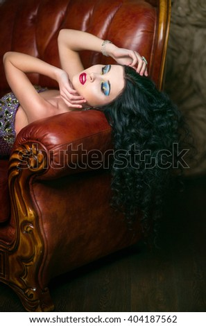 Beautiful brunette girl in a violet cocktail dress for holiday parties lies in the leather chair - stock photo