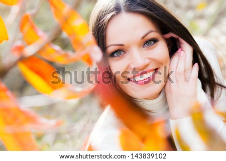 Beautiful brunette girl in autumn peach garden - stock photo