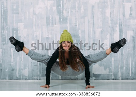 Beautiful brunette girl in funny knitted green hat and casual clothes stay in gymnastic pose and smile. Slim gymnast posing. Balance pose. Handstand  - stock photo