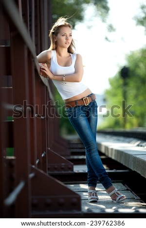 Beautiful brunette girl in jeans and a t-shirt posing on railroad tracks - stock photo