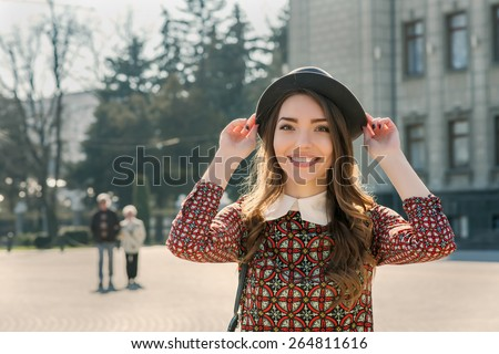Beautiful brunette girl in stylish dress posing on the city square. Fashion and city style. Facial expression. Various flags and the Orthodox Church on background. - stock photo