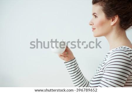 Beautiful brunette girl is enjoying hot drink - stock photo