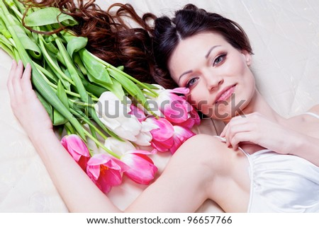 Beautiful brunette girl laying in bed with tulip flowers - stock photo